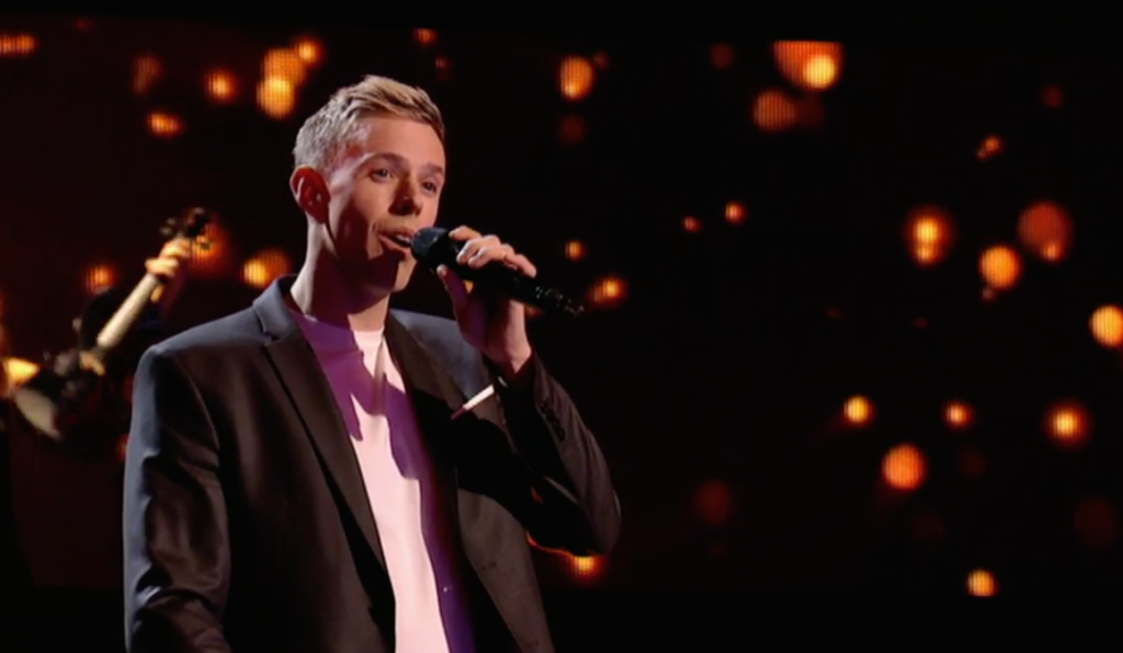 Stephen Barry singing holding a microphone wearing a dark jacket and a light pink tee shirt.  Dark background with lols of small lights